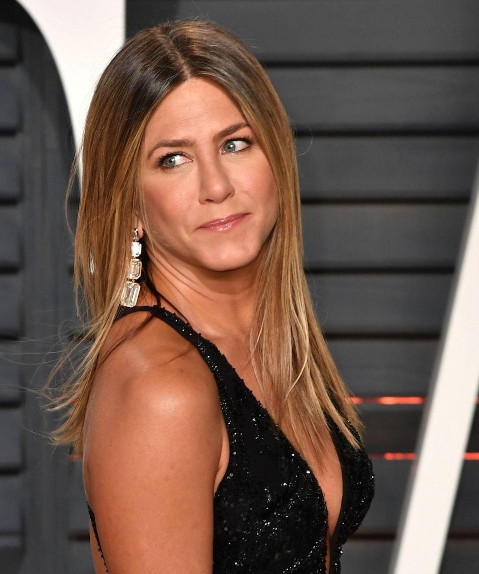 """<p>At the 2017 Vanity Fair Oscars party, Jen trades in her go-to all-over blonde color for this dark-rooted style. She still keeps her honey highlights, but wears them instead in a gradual, lived-in <a href=""""https://www.goodhousekeeping.com/beauty/hair/g3279/balayage-hair-color/"""" rel=""""nofollow noopener"""" target=""""_blank"""" data-ylk=""""slk:balayage"""" class=""""link rapid-noclick-resp"""">balayage</a>. </p>"""