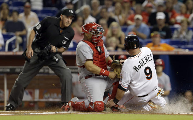 Miami Marlins' Casey McGehee (9) is tagged out at home plate by Cincinnati Reds catcher Brayan Pena as McGehee tried to score from second base on a base hit by Garrett Jones in the first inning of a baseball game in Miami, Thursday, July 31, 2014. Home plate umpire Mike Winters, left, watches the play. (AP Photo/Alan Diaz)
