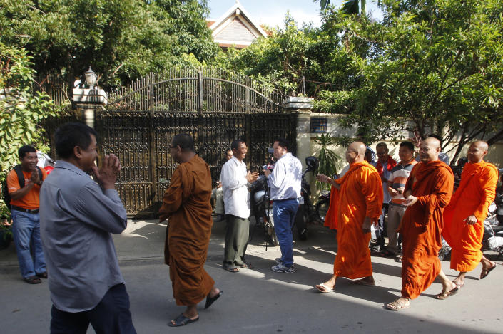 Cambodian Buddhist monks arrive in front of the house of Kem Sokha, former leader of now dissolved opposition Cambodia National Rescue Party, in Phnom Penh, Cambodia, Monday, Sept. 10, 2018. Kem Sokha was released on bail Monday after being jailed for a year on a treason charge, a government spokesman said. A small crowd has gathered outside his home in Phnom Penh but so far he hasn't been seen. His whereabouts are, as yet, unclear. (AP Photo/Heng Sinith)