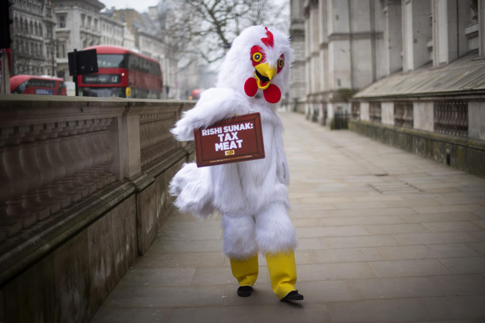 An animal rights activist dressed as a chicken with sign calling on Chancellor of the Exchequer Rishi Sunak to tax meat, outside Downing Street in London Wednesday March 3, 2021. Sunak is expected to announce tax and spending projections to help workers and businesses hit by the coronavirus pandemic when he delivers his budget to Parliament later Wednesday. (Victoria Jones/PA via AP)