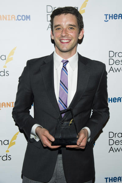 """FILE - This May 19, 2013 file photo shows Michael Urie holding his award for outstanding solo performance for his role in """"Buyer & Cellar,"""" at the 2013 Drama Desk Awards in New York. The Juilliard-trained Urie plays a struggling actor who lands a job as a clerk in an underground mall of quaint shops. (Photo by Charles Sykes/Invision/AP, file)"""
