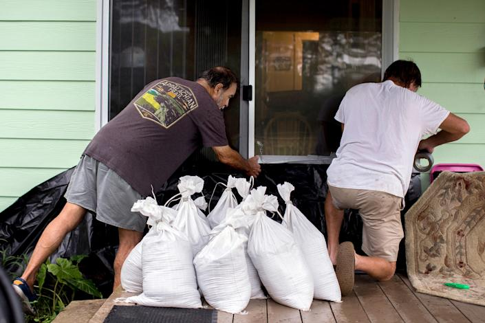 """Tony Pagan, left, helps a friend set sandbags in place over a plastic tarp on the back door as they prepare to evacuate before Hurricane Dorian arrives with its storm surge and tropical storm winds, Wednesday, Sept. 4, 2019, in Tybee Island, Ga. """"This is climate change, though President Trump denies that it is,"""" Pagan, a 69-year-old retired electrician said as he and his wife finished packing to evacuate Wednesday. """"He needs to open his eyes."""" (AP Photo/Stephen B. Morton)"""