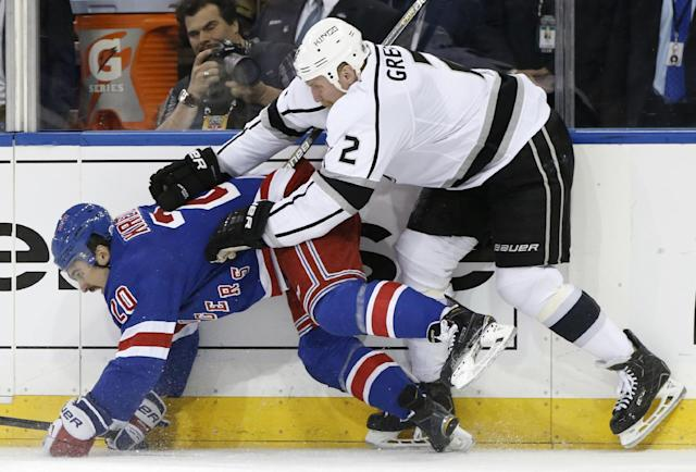 New York Rangers left wing Chris Kreider (20) hits the boards with Los Angeles Kings defenseman Matt Greene (2) in the second period during Game 4 of the NHL hockey Stanley Cup Final, Wednesday, June 11, 2014, in New York. (AP Photo/Kathy Willens)