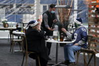 """Tom Gallagher, right, wears a Seattle Seahawks Julian Peterson jersey and holiday hat as he is offered a bottle of wine by a server while dining with his wife Debbie in an outdoor dining tent set up on the turf at Lumen Field, Thursday, Feb. 18, 2021, in Seattle. The couple, who are Seattle Seahawks season ticket holders, were celebrating their 45th anniversary by taking part in the """"Field To Table"""" event at the Seahawks' home stadium on the first night of several weeks of dates that offer four-course meals cooked by local chefs and served at tables socially distanced as a precaution against the COVID-19 pandemic. (AP Photo/Ted S. Warren)"""