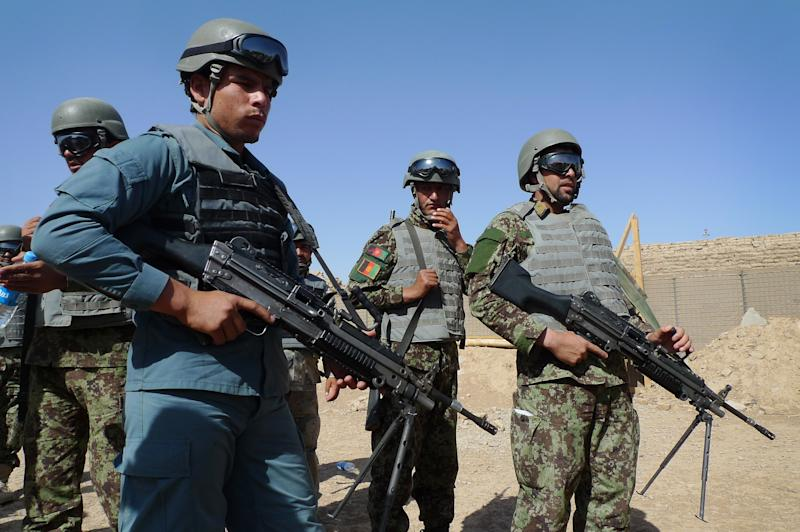 "In this June 19, 2012 file photo, Afghan soldiers and a policeman  prepare for a mock ambush as part of a training exercise at the U.S. Marine-run Joint Sustainment Academy, Camp Leatherneck in Helmand, south of Kabul.  The U.S. suspects the Haqqani insurgent network, which has ties to al-Qaida and is based in Pakistan, is a driving force behind many of the ""insider"" attacks by Afghan forces that have killed more than 50 U.S. and allied troops this year, officials say. Until now, officials have said the attacks seemed to stem either from personal grievances against the allies or from Taliban infiltration.  (AP Photo/Heidi Vogt)"