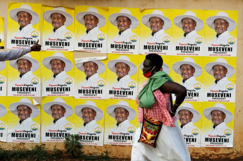 A woman walks past elections posters of Uganda's President Yoweri Museveni on a street in Kampala