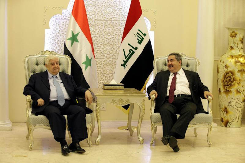 Iraqi Foreign Minister Hoshyar Zebari, right, and his Syrian counterpart Walid al-Moallem, talk during a meeting in Baghdad, Iraq, Sunday, May 26, 2013. (AP Photo/Hadi Mizban, Pool)