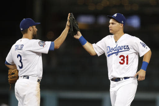 Los Angeles Dodgers' Chris Taylor, left, and Joc Pederson celebrate their team's 12-5 win against the Texas Rangers in a baseball game Tuesday, June 12, 2018, in Los Angeles. (AP Photo/Jae C. Hong)