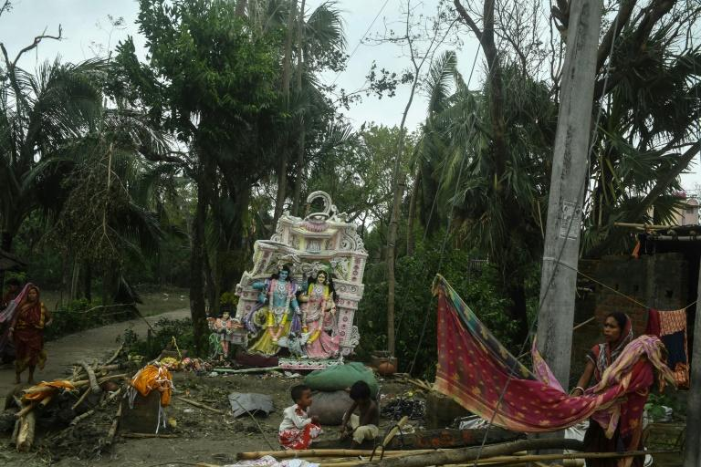 A resident hangs washing out to dry as kids play near a damaged Hindu idol following the landfall of Cyclone Amphan in the Khejuri area of Midnapore, West Bengal, on May 21, 2020