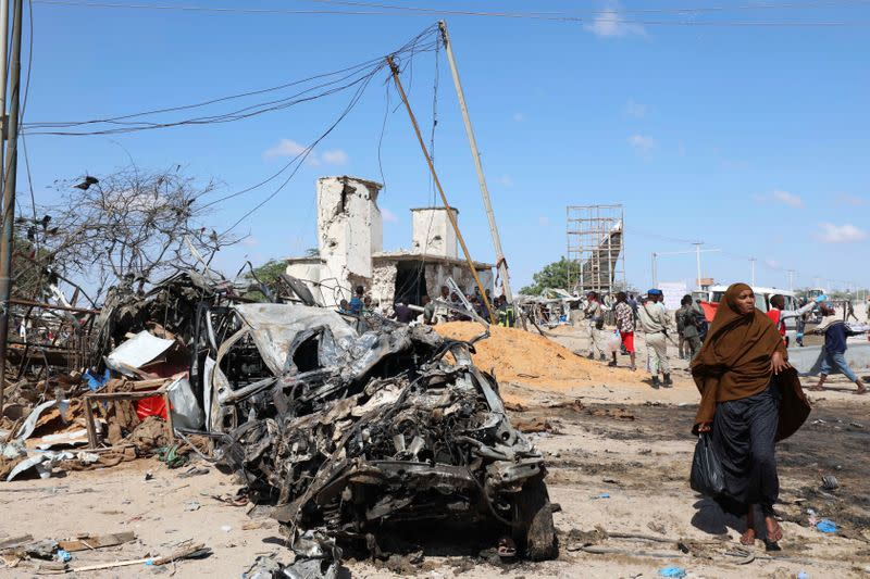 A Somali woman walks past a wreckage at the scene of a car bomb explosion at a checkpoint in Mogadishu