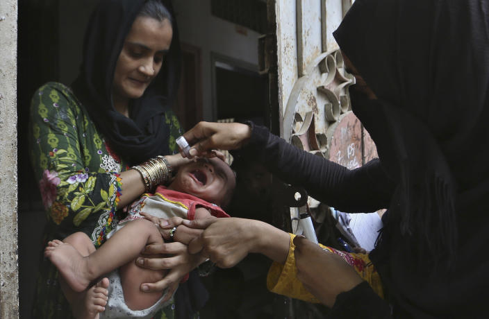 A health worker administers a polio vaccine to a child, in Karachi, Pakistan, Wednesday, June 9, 2021. Gunmen on a motorcycle Wednesday shot and killed two police officers assigned to protect polio vaccination workers in the district of Mardan in Khyber Pakhtunkhwa province, northwest Pakistan before fleeing, police said. (AP Photo/Fareed Khan)
