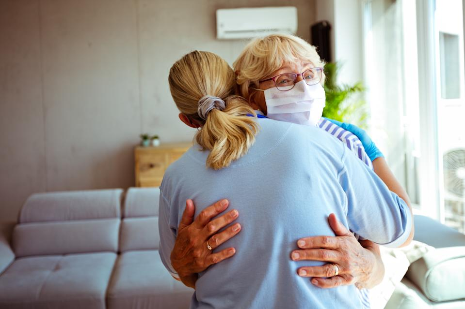 District nurse embracing worried with senior woman during home visit. They are standing in living room.