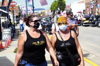 FILE - In this Aug. 7, 2020, file photo, women walk during opening day of the 80th annual Sturgis Motorcycle Rally in Sturgis, S.D. The rally refused to take 2020 off despite the threat of the coronavirus pandemic, a decision blamed for leading to a late-summer spike in cases across the Midwest. And it's about to roar right back this year, kicking off Friday, Aug. 6, 2021 with crowds expecting to be significantly larger even as the delta variant is rising. (AP Photo/Stephen Groves, File)