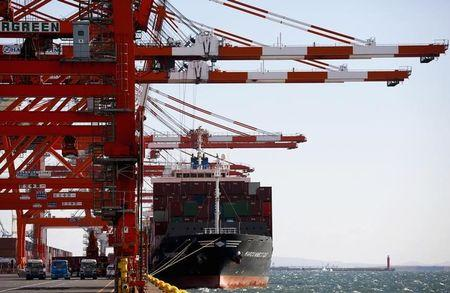 A container ship is loaded at a port in Tokyo