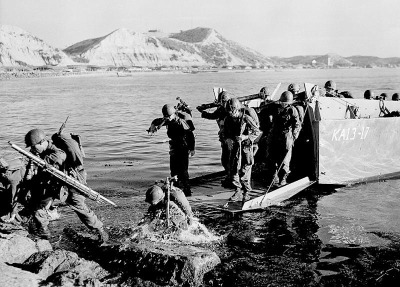 FILE - In this July 19, 1950 black-and-white file photo, troops of the First U.S. Cavalry Division land ashore at Pohang on the east coast of Korea during the Korean War. The hunt for thousands of fallen American troops like Robert Schmitt missing from a conflict fought six decades ago is about to resume in North Korea as tensions ease between the wartime enemies. (AP Photo, File)