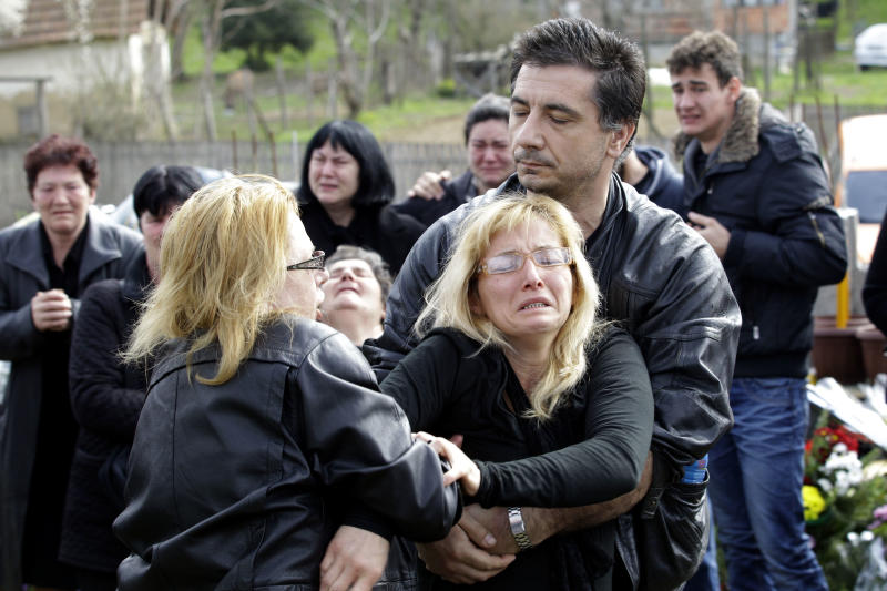 Relatives of victims of a shooting react prior to a mass funeral in the village of Velika Ivanca, some 50 kilometers (30 miles) southeast of Belgrade, Serbia, Friday, April 12, 2013. The village of Velika Ivanca is preparing for the funerals of thirteen victims of a shooting that happened on Tuesday, April 9, 2013. Ljubisa Bogdanovic, a local and a Yugoslav wars veteran, went from house to house on April 9 in the village at dawn, cold-bloodedly gunning down his mother, his son, a 2-year-old cousin and ten other neighbors. (AP Photo/ Darko Vojinovic)