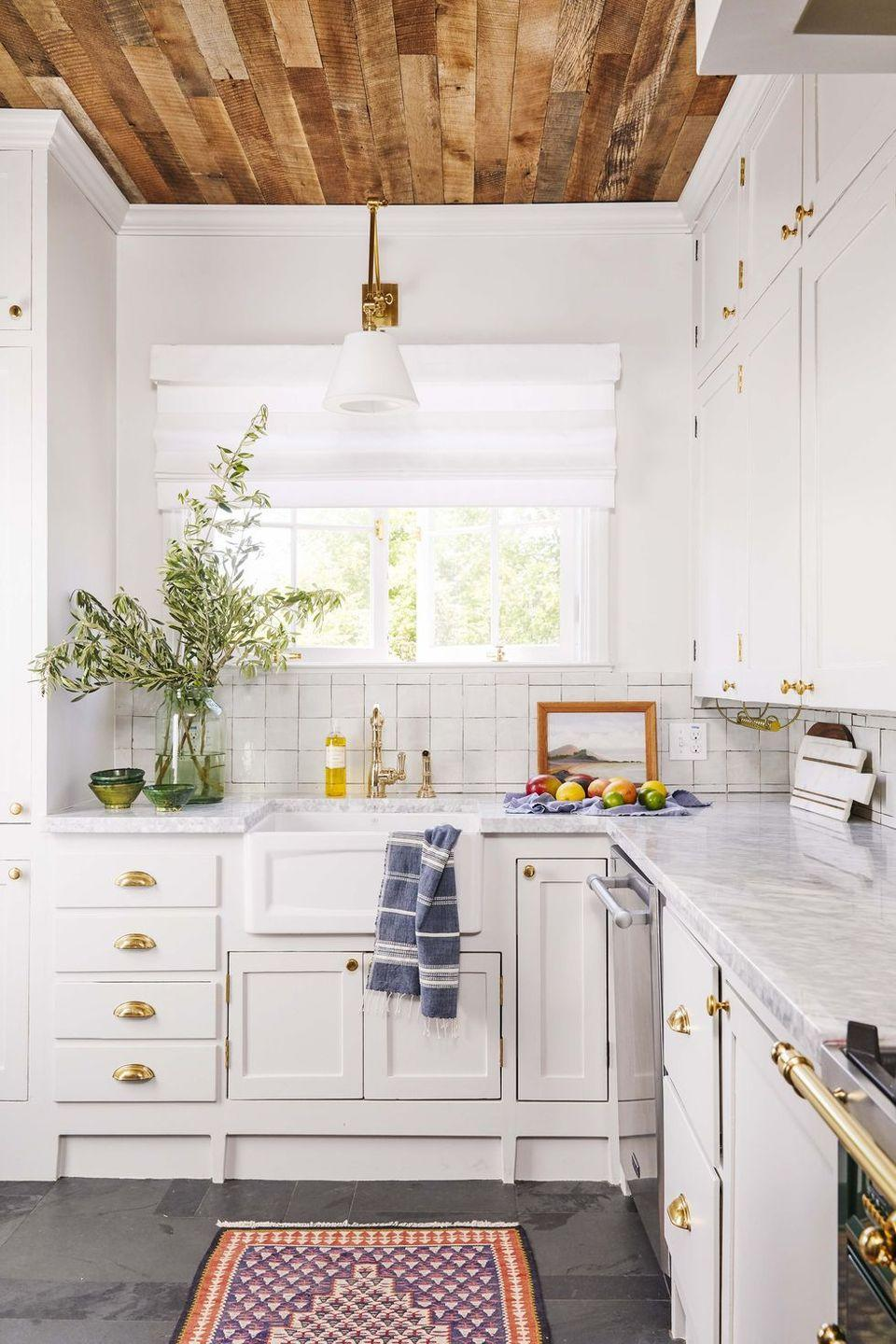 """<p>Designer <a href=""""https://murphydeesign.com/"""" rel=""""nofollow noopener"""" target=""""_blank"""" data-ylk=""""slk:Dee Murphy"""" class=""""link rapid-noclick-resp"""">Dee Murphy</a> gave her family kitchen a new life by repainting the cabinets, swapping out hardware, installing task lighting, and sprucing up the window treatments. But what really makes it feel homey and historied are the unique and handmade qualities of the surfaces, from the zellige tile backsplash to the stone tile floors and rustic wood paneled ceiling. The variation in the wood panels brings so much character. </p>"""