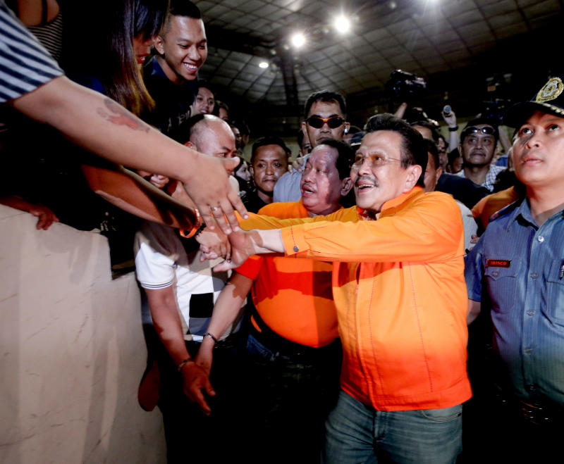 """Former Philippine President and now Mayor-elect Joseph """"Erap"""" Estrada is congratulated by supporters shortly after his proclamation by the City Board of Canvassers of the Commission Elections Tuesday May 14, 2013, a day after the country's automated midterm elections in Manila, Philippines.  Former President Estrada was proclaimed Tuesday as the new mayor of the Philippine capital, his first elected post since he was ousted in an anti-corruption revolt 12 years ago. (AP Photo/Bullit Marquez)"""