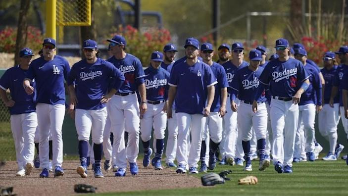 Los Angeles Dodgers players walk back to the infield after running sprints during a spring training baseball practice Tuesday, Feb. 23, 2021, in Phoenix. (AP Photo/Ross D. Franklin)