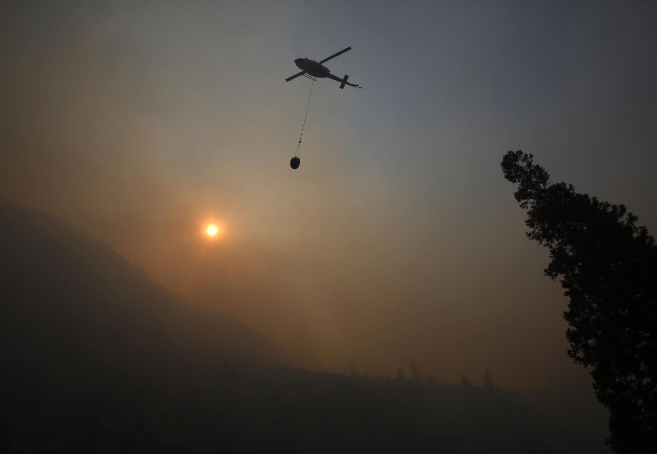 A fire helicopter takes off through smoke rising to make a drop on active fires in Yosemite National Park after the park reopened after a three week closure from smoke and fires that led to most tourists canceling their trips Tuesday, Aug. 14, 2018 in Yosemite, Calif. (AP Photo/Gary Kazanjian)