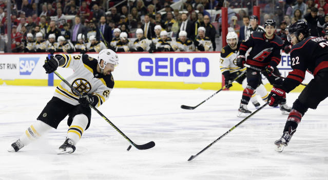 Boston Bruins' Brad Marchand (63) controls the puck against Carolina Hurricanes' Brett Pesce (22) during the first period in Game 3 of the NHL hockey Stanley Cup Eastern Conference final series in Raleigh, N.C., Tuesday, May 14, 2019. (AP Photo/Gerry Broome)
