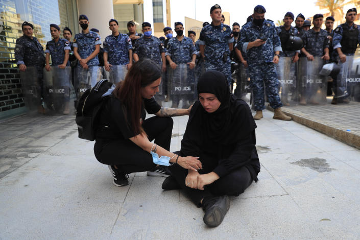 A woman from the Families of the victims of last year's massive blast at Beirut's seaport, left, comforts a woman who fall down while she was trying with other to reach the tightly-secured residents of parliament speaker Nabih Berri and pushed back by Lebanese army soldiers, in Beirut, Lebanon, Friday, July 9, 2021. The protest came after last week's decision by the judge to pursue senior politicians and former and current security chiefs in the case, and requested permission for their prosecution. (AP Photo/Hussein Malla)
