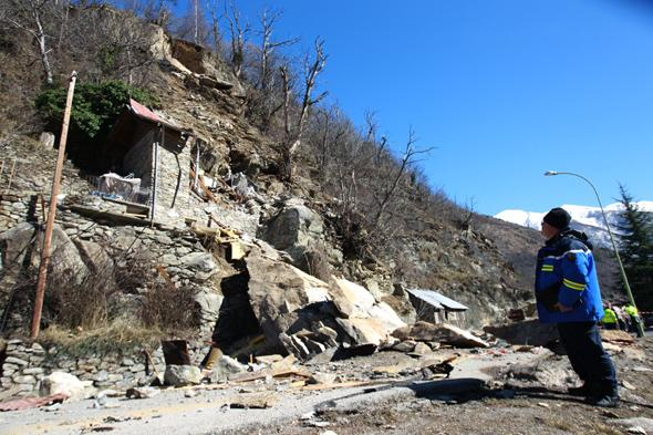 A French Gendarme looks at, on February 23, 2014 in Isola Village (French Alps), the mountain cottage destroyed by a rockslide which killed two children aged seven and ten. AFP PHOTO / JEAN CHRISTOPHE MAGNENET        (Photo credit should read JEAN CHRISTOPHE MAGNENET/AFP/Getty Images)