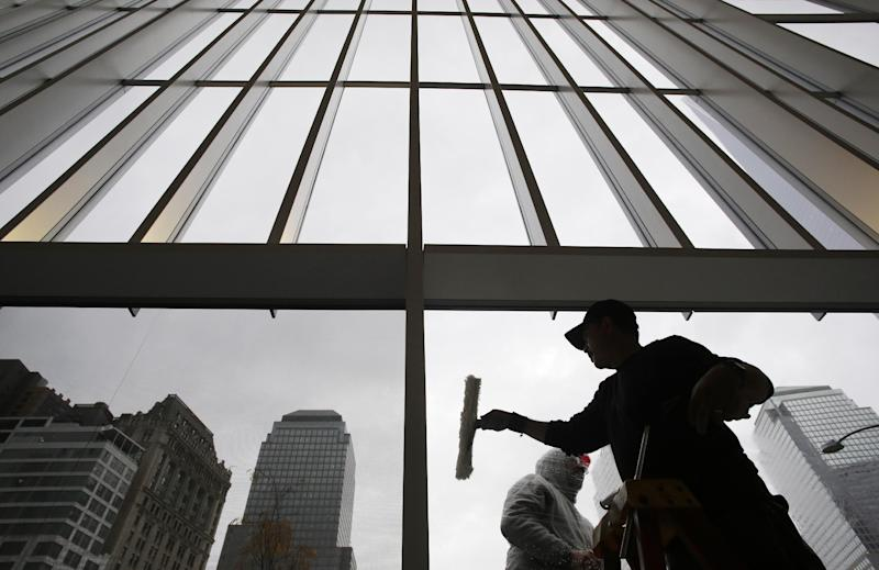 Workers clean the glass windows at the lobby of 4 World Trade Center, Thursday, Nov. 7, 2013, in New York. The 1,776-foot One World Trade Center is the marquee skyscraper at ground zero; but the first office tower to open there will be its shorter neighbor 4 World Trade Center on Wednesday, Nov. 13. (AP Photo/Mark Lennihan)