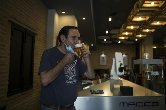 Albero Marinez, owner of the 'La Gitana Loca' bar says he bought the robot before the epidemic took hold hoping to boost sales (AFP Photo/CRISTINA QUICLER)