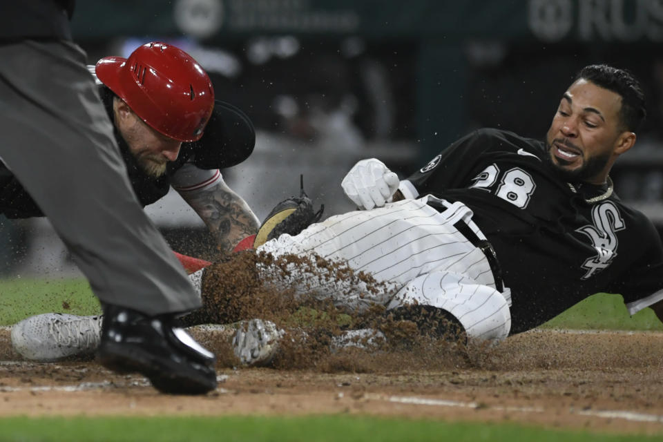 Chicago White Sox's Leury Garcia (28) slides into home plate while being tagged out by Cincinnati Reds catcher Tucker Barnhart right, while trying for an inside the park home run during the fourth inning of a baseball game Tuesday, Sept. 28, 2021, in Chicago. (AP Photo/Paul Beaty)