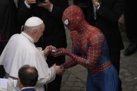 Pope Francis meets Spider-Man, who presents him with a mask, at the end of his weekly general audience with a limited number of faithful in the San Damaso Courtyard at the Vatican, Wednesday, June 23, 2021. The masked man works with sick children in hospitals. (AP Photo/Andrew Medichini)