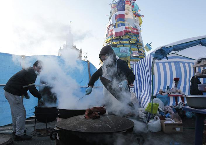 Pro-European Union activists cook meals during a rally in the Independence Square in Kiev in Kiev, Ukraine, Thursday, Dec. 26, 2013. (AP Photo/Sergei Chuzavkov)