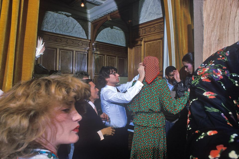 Yves Saint Laurent adjusting models backstage at his Paris collection in 1993. His muse, Loulou de la Falaise, is pictured in the foreground, and the famed hairdresser Alexandre is behind Saint Laurent. Photographed for French Vogue.