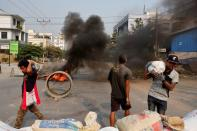 Demonstrators set up barricades during a protest against the military coup in Mandalay