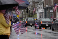 """People display American flags as a hearse, center, carrying the coffin of the late U.S. Capitol Police officer William """"Billy"""" Evans, left, drives though downtown Adams, Mass., following a funeral Mass for Evans, Thursday, April 15, 2021. Evans, a member of the U.S. Capitol Police, was killed on Friday, April 2, when a driver slammed his car into a checkpoint he was guarding at the Capitol. (AP Photo/Steven Senne)"""
