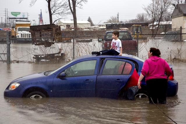 <p>Flint resident Brayden Bend, 5, sits on top of his mother's friend's vehicle on Robert T. Longway Boulevard at North Center Road on Tuesday, Feb. 20, 2018, in Flint, Mich. High flood waters caused several motorists to become stuck. (Photo: Bronte Wittpenn/The Flint Journal-MLive.com via AP) </p>