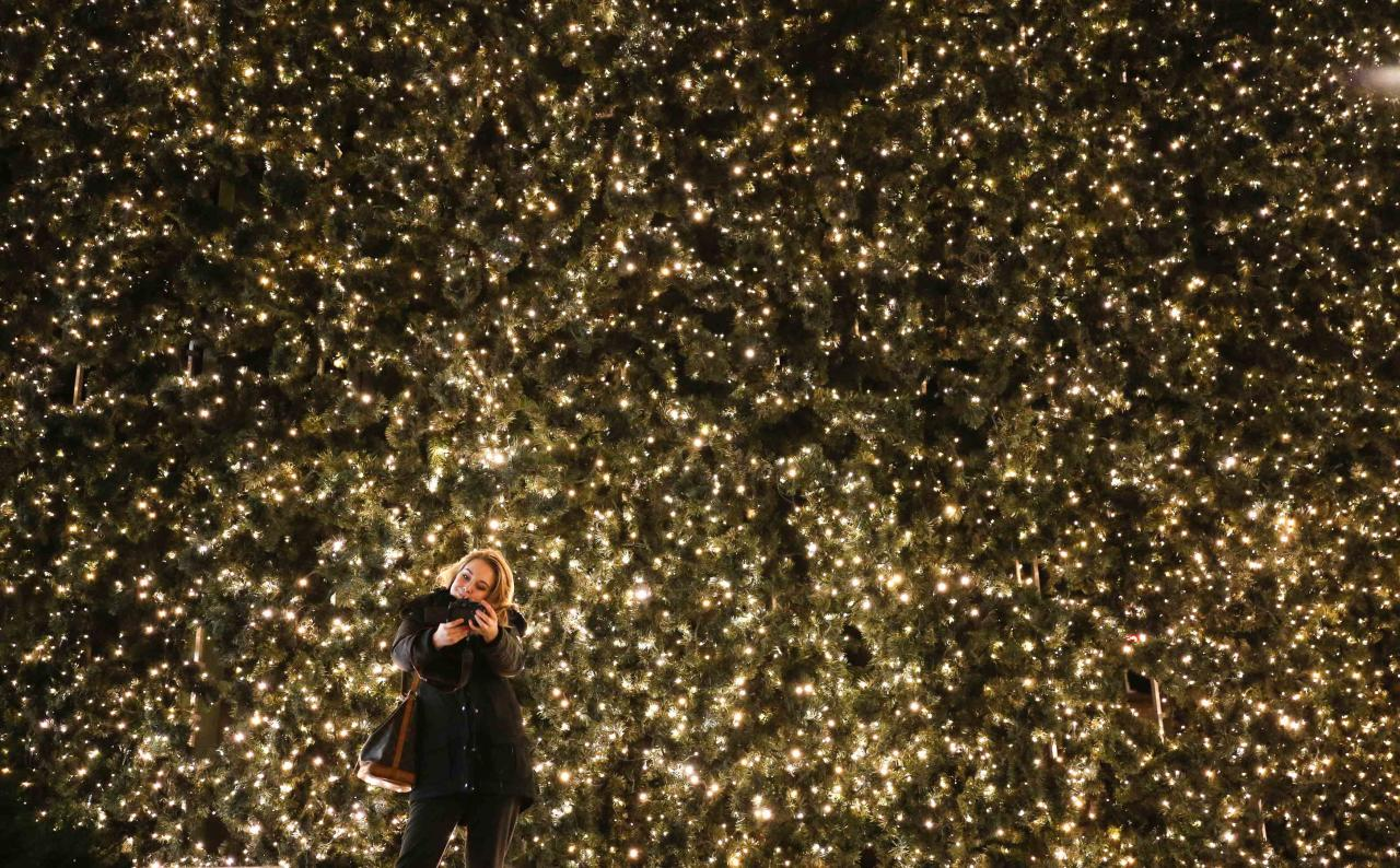 A woman takes a picture of herself with part of the Christmas illumination of the main shopping mall Kurfuerstendamm boulevard in Berlin