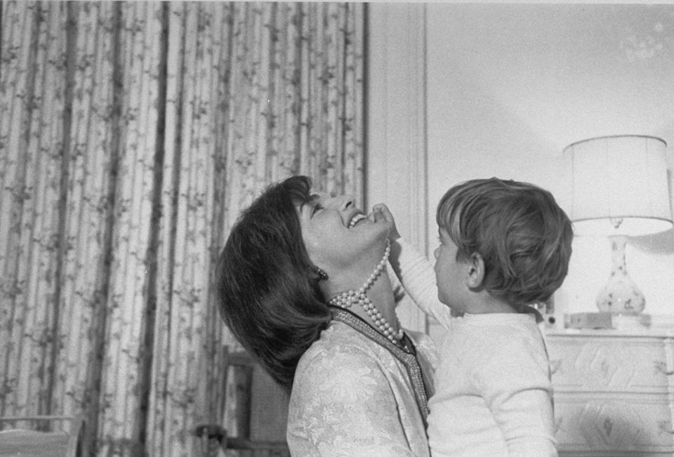 <p>John F. Kennedy Jr. is seen playing with his mother's pearls. </p>