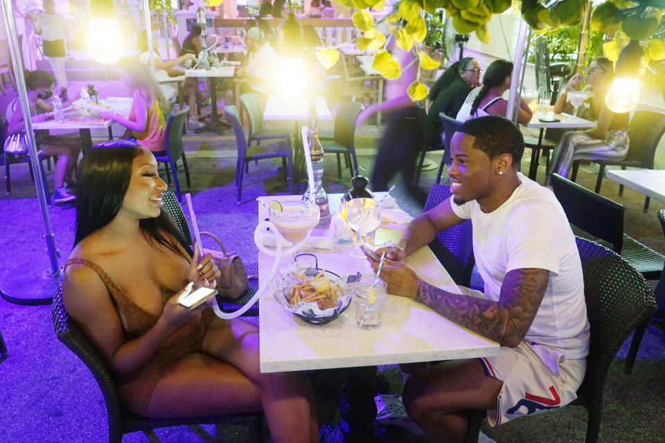 Yakima Carpenter of New Jersey and her boyfriend Anthony Phillips of New York, enjoy dinner, drinks and smoking a hookah, Wednesday, Sept. 15, 2021, in Miami Beach, Fla. For decades, the 10-block area of South Beach has been the most glamorized spots in the world. But in recent years, the glitter is wearing off amidst increasingly violent crimes and vandalized businesses. (AP Photo/Marta Lavandier)