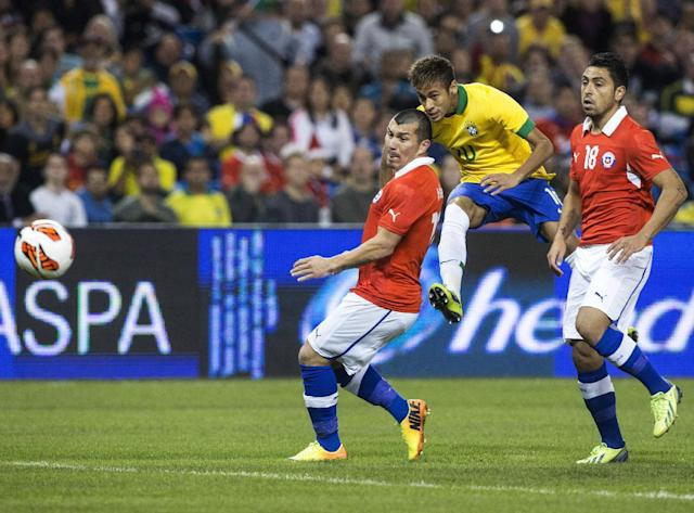 Brazil's Neymar , center, gets a shot away under pressure from Chile's Gonzalo Jara. right, and Gary Medel during first half action of their international friendly match in Toronto on Tuesday Nov. 19, 2013. (AP Photo/The Canadian Press, Chris Young)