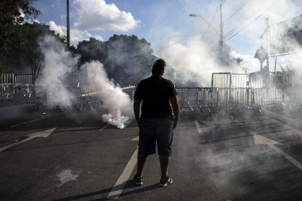 A man challenges police officers during a protest outside the Mineirao stadium during the soccer Confederations Cup semifinal match between Brazil and Uruguay in Belo Horizonte, Brazil, Wednesday, June 26, 2013. The wave of protests that hit Brazil on June 17 began as opposition to transportation fare hikes, then expanded to a list of causes including anger at high taxes, poor services and high World Cup spending, before coalescing around the issue of rampant government corruption. (AP Photo/Felipe Dana)