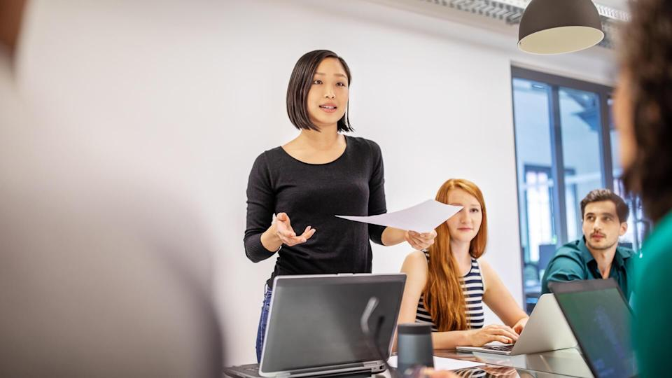 Confident female professional discussing in board room.
