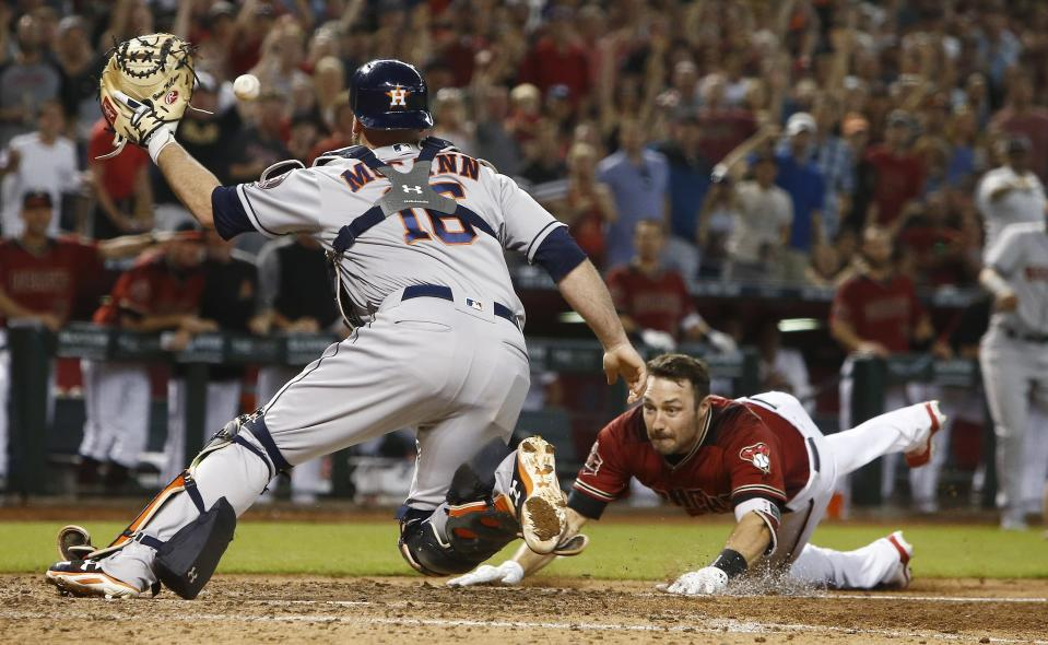 Arizona Diamondbacks' A.J. Pollock (R) dives into home plate as Houston Astros catcher Brian McCann (L) reaches to catch the ball during the sixth inning of a baseball game Sunday, May 6, 2018, in Phoenix. (AP Photo/Ross D. Franklin)