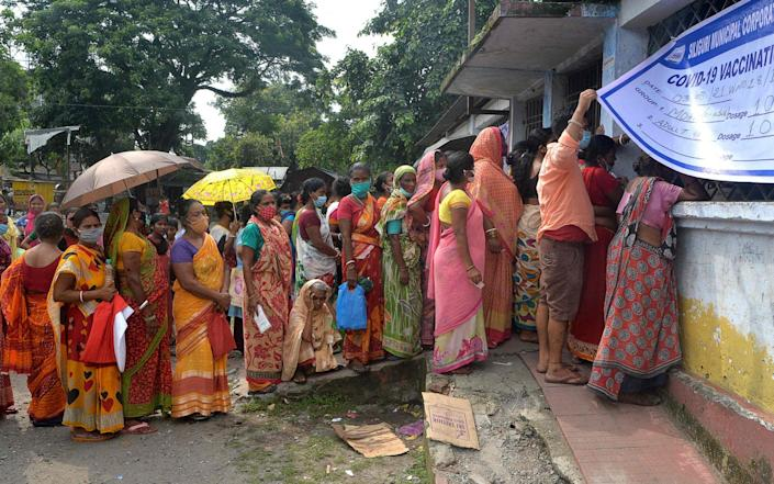 People queue to receive a dose of the Covishield vaccine at a primary school in Siliguri, India on 3 August 2021 - Diptendu Dutta/AFP