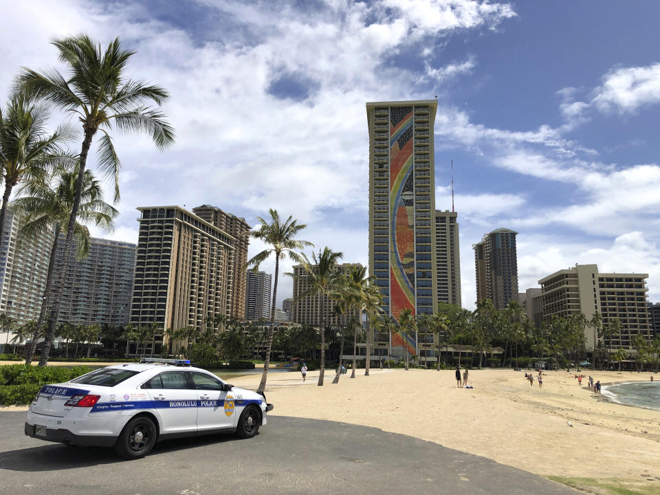 """FILE - In this March 28, 2020 file photo a police officer arrives to tell people to leave Waikiki Beach in Honolulu. Former Hawaii television reporter Angela Keen knows how to track people down. During the coronavirus pandemic, she's putting her people-finding skills to use as one of the original members of a Facebook group that has grown to more than 2,000 people called """"Hawaii Quarantine Kapu Breakers."""" Kapu is a Hawaiian word that means laws or rules. The group is focused on finding people who violate Hawaii's 14-day quarantine on travelers arriving to the state. (AP Photo/Caleb Jones,File)"""