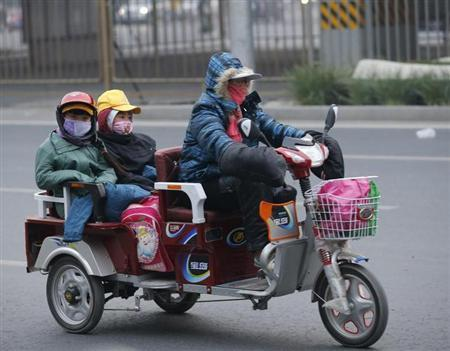 A woman and her children wearing masks ride a vehicle during a smoggy day in Beijing