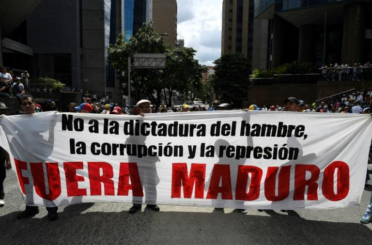"""Supporters of Venezuelan opposition leader Juan Guaido hold a banner reading """"Maduro Out"""" as they protest against President Nicolas Maduro in Caracas"""