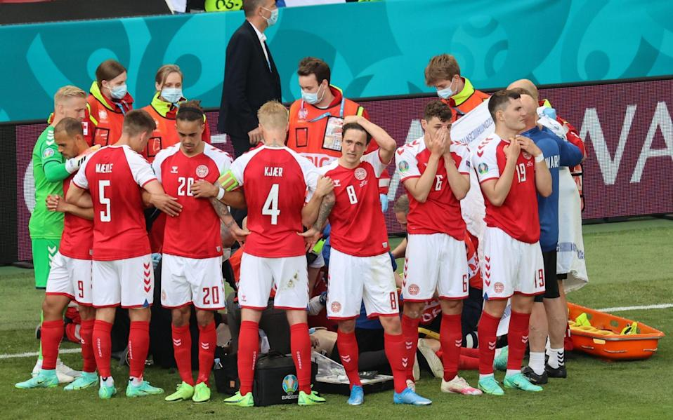 Christian Eriksen's teammates form a protective ring around him on Saturday. The Danish midfielder received chest compressions on pitch - Shutterstock/Wolfgang Rattay/POOL/EPA-EFE/Shutterstock