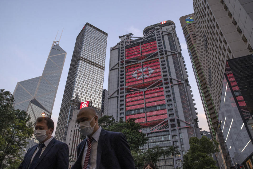 Pedestrians wearing protective masks walk as the HSBC Holdings Plc headquarters building, center, stands illuminated in the Central district of Hong Kong, China, on Monday, April 27, 2020. | Roy Liu/Bloomberg via Getty Images