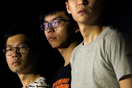 """Hong Kong student leaders of the """"Umbrella Movement"""" Nathan Law and Joshua Wong attend a rally against """"the cooperation of three powers"""", a day before an appeal verdict on charges relating to 2014 pro-democracy, also known as """"Occupy Central"""", protests, in Hong Kong, China August 16, 2017. REUTERS/Tyrone Siu"""
